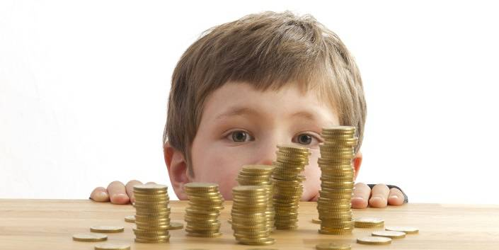 Child behind piles of coins