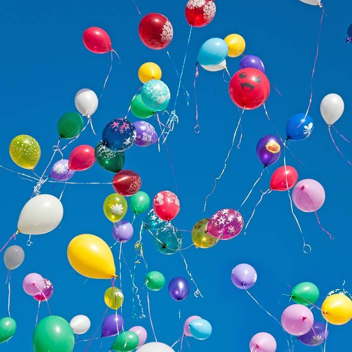 Lots of colourful balloons flying into the sky