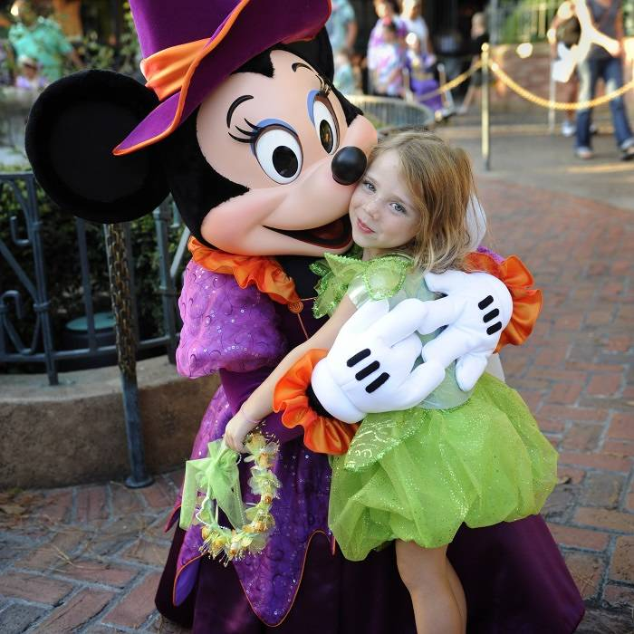 Minnie Mouse hugs a girl dressed as a fairy