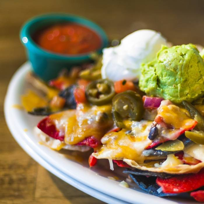 Plate of nachos with melted cheese and guacamole