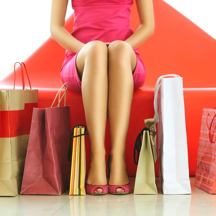 Woman sitting surrounded by shopping bags