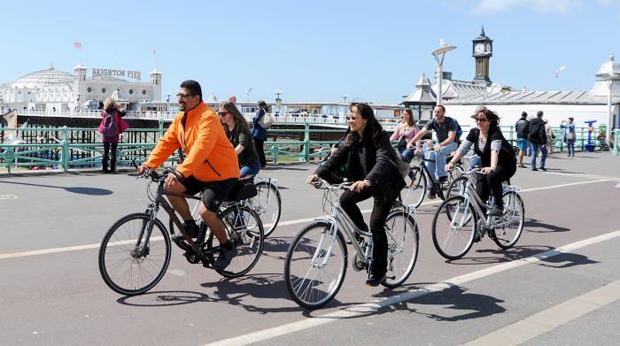 Cyclists exploring Brighton seafront in the sun