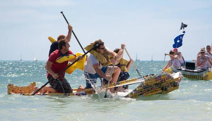picture of people paddling in a beer can boat